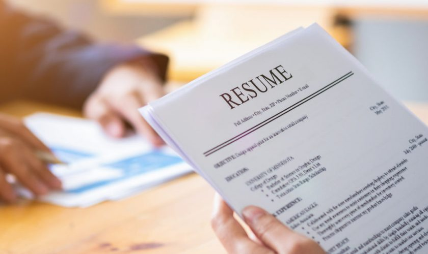 Interviewer reading a resume, Person submits job application, Person describe yourself to interviewer, Close up view of job interview in office, focus on resume, recruiter considering application, hr manager making hiring decision